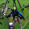 Terrified hang glider student hangs on with one hand over beautiful scenery
